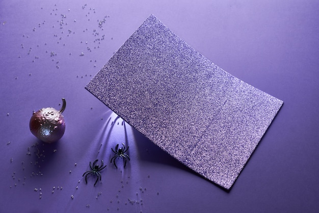 Creative purple halloween mockup with two glittering pumpkins painter metallic color with spiders crawling along long shadows underneath shining paper card, copy-space