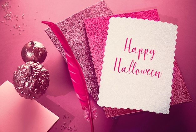 Creative purple and pink halloween mockup with levitating pink pin quill, stack of glittering paper and decorative pumpkins painted metallic pink