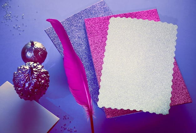 Creative purple and pink halloween mockup with levitating pink pin quill, stack of glittering paper and decorative pumpkins