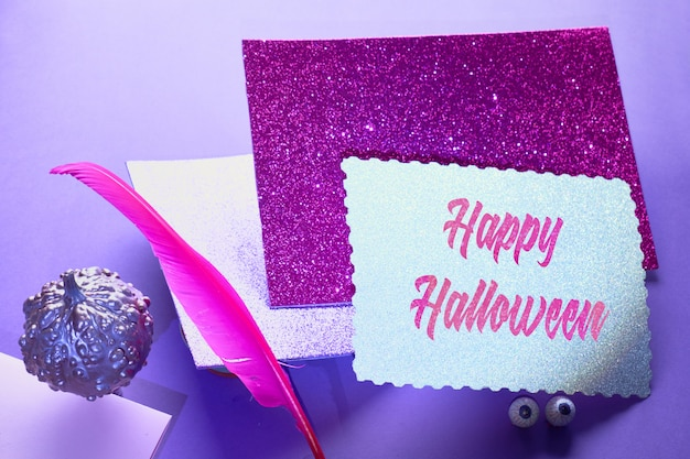 Creative purple and pink halloween table with levitating pink pin quill, stack of glittering paper and pumpkins