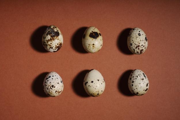 茶色の背景にクリエイティブなウズラの卵のレイアウト。ウズラの卵のパターン。ハッピーイースターのコンセプト。最小限のデザイン。