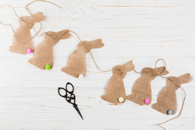 Creative rabbit shape bunting with scissor over wooden surface