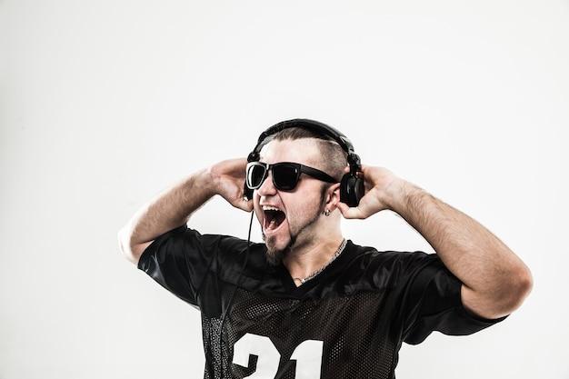 Креативный рэпер в наушниках и темных очках исполняет рэп-песню.