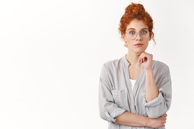 Creative redhead curly woman comb hair in messy-bun, wear glasses look focused and curious, listen carefully interesting idea, contemplate interesting painting, touch chin, gaze at front thoughtful