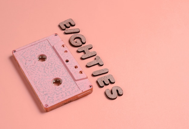 Creative retro style concept, 80s. audio cassette on vanilla pink with the word eighties from wooden letters