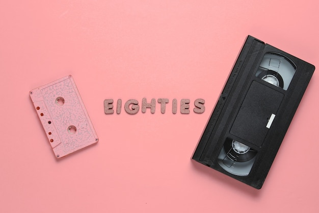 Creative retro style concept, 80s. audio and video cassette on pink with the word eighties from wooden letters