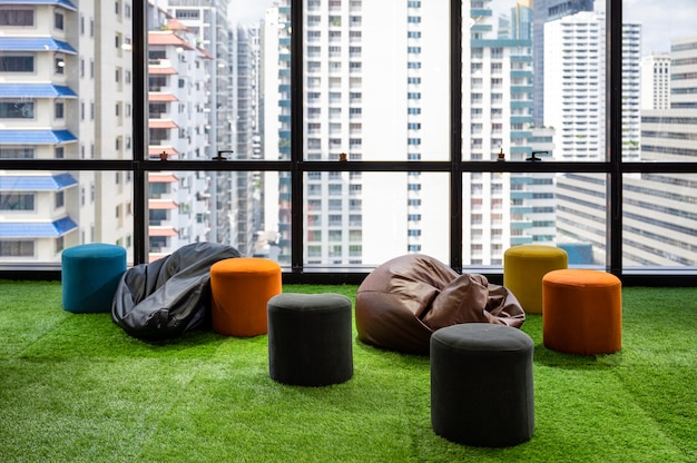 モダンなオフィスの人工芝にクッションと椅子を備えたクリエイティブルームのコワーキングスペース