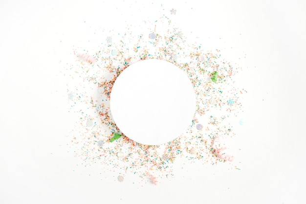 Creative round layout with copy space made of colorful confetti on white background. celebration concept background. flat lay