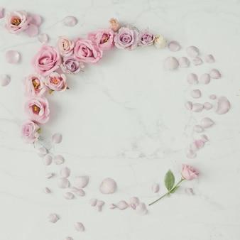 장미 꽃과 꽃잎으로 만든 크리 에이 티브 라운드 화환 프레임.