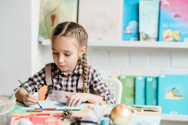 Creative schoolgirl with paintbrush sitting by desk and drawing christmas picture with paints in classroom