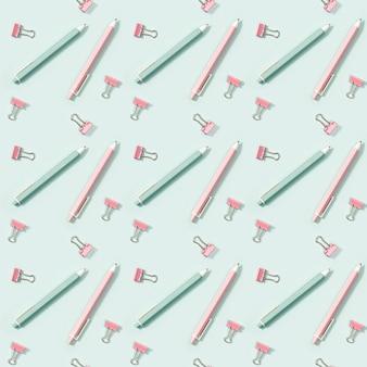 Креативный бесшовный образец с канцелярскими принадлежностями розового и зеленого цвета, ручками и металлическими скрепками