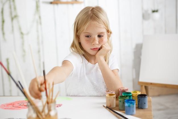 Творческая семилетняя девочка рисует акварелью, сидит за столом и кладет локти на стол