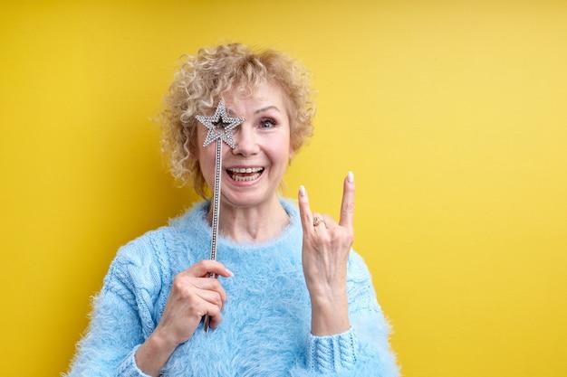 魔法の杖を持つ美しい狂気の年配の女性の創造的なショット、ロックジェスチャーを示す、笑顔、黄色で隔離のポーズ