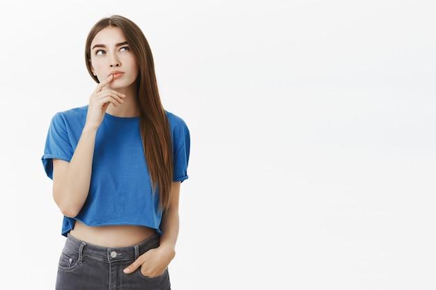 Креативная, умная и вдумчивая привлекательная европейская женщина в модном синем укороченном топе делает жест пальцем на нижней губе, приподнимая бровь и глядя вверх, думая, делая выбор в уме