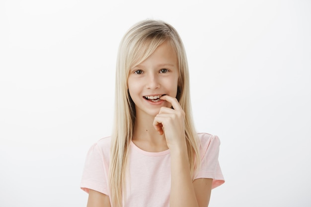 Creative smart kid made up great idea. portrait of dreamy cute girl with fair hair, smiling joyfully and biting finger, having plan or wanting to make something intriguing, standing over gray wall