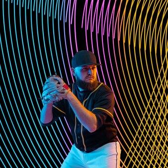 Творческий спорт на фоне темной неоновой подсветкой линии. тренировка бейсболиста в действии и движении на красочных волнах. понятие хобби, здорового образа жизни, молодежи, действия, движения, современного стиля. Premium Фотографии