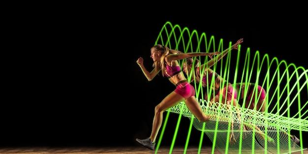 Творческий спорт на фоне темной неоновой подсветкой линии. профессиональная тренировка бегунов в действии и движении на разноцветных волнах. понятие о хобби, здоровом образе жизни, молодежи, движении, современном стиле. листовка.