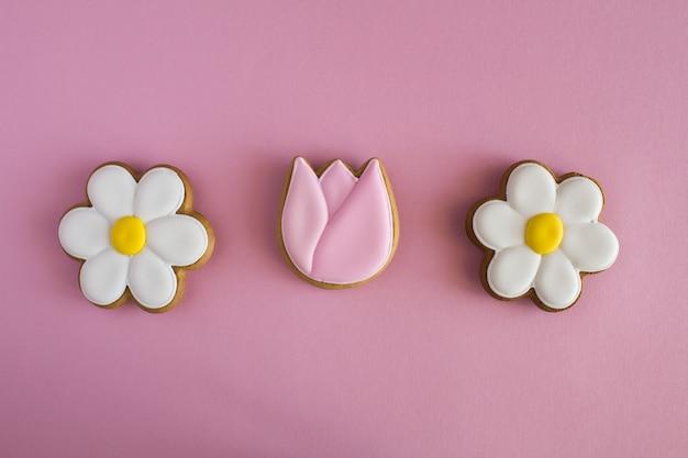 創造的な春の背景。ピンクの背景にジンジャーブレッドの形の花。上面図。コピースペース。