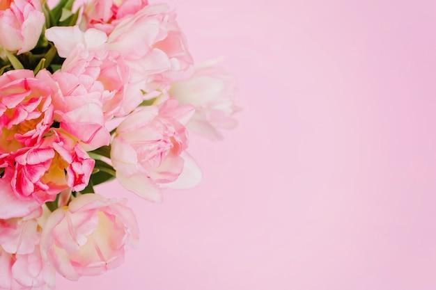 ピンクの背景に創造的な春の構成カラフルなチューリップ