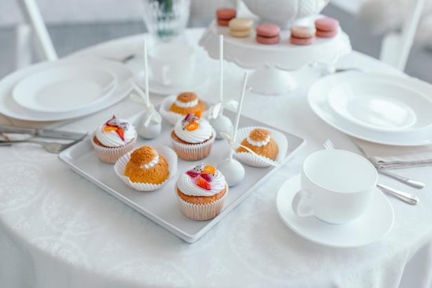 創造的な春の組成。エレガントな甘いデザートマカロン、紅茶またはコーヒーカップ、美しいパステルカラーのベージュとサンゴの花の花束