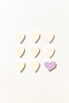 Креативный квадратный узор из маленьких бумажных сердечек ручной работы и одно из них розовое на светло-серой стене с мягкими тенями, копией пространства. валентина вид сверху.