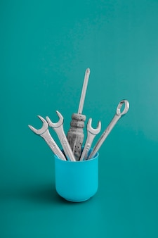 Creative still life in minimalism style, vase with working tools: screwdriver, wrenches on a colored background. concept greeting card
