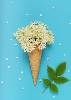 ターコイズブルーの背景にニワトコの花とアイスクリームワッフルコーンの創造的な静物。上面図。