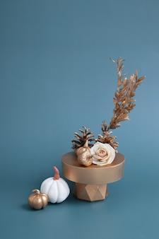 ターコイズブルーの背景に金と白のカボチャ、どんぐり、バラの創造的な静物。ミニマルな秋のコンセプト