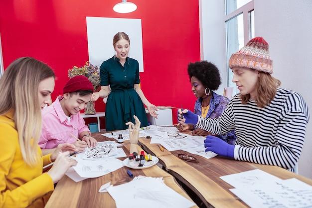 創造的な学生。先生に耳を傾けるファッション学科の4人の創造的なファッショナブルな学生