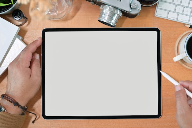 Creative stylish hand holding blank screen drawing tablet and pencil