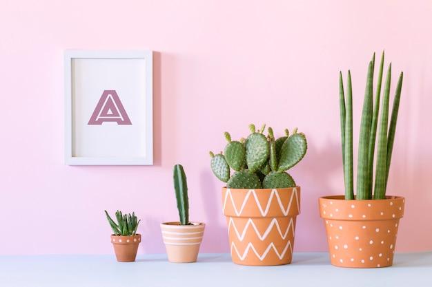 モックアップポスターフレームと植物ピンクの壁のテンプレートと創造的なスタイリッシュなヒップスターのインテリアデザイン