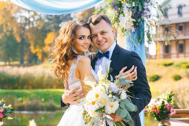 創造的なスタイリッシュな結婚式エレガントな巻き毛の花嫁と花婿の屋外の背景に湖