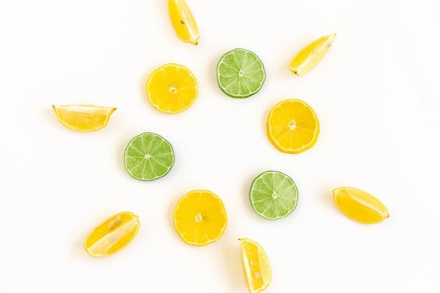 レモンとライムのスライスで創造的な夏の背景の構成フラットレイパターン夏のコンセプト