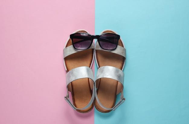 創造的な夏のビーチフラットが横たわっていた。レザーレディースサンダル、ブルーピンクのサングラス。