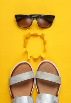 創造的な夏のビーチフラットが横たわっていた。レザーレディースサンダル、破れた穴のある黄色のサングラス。