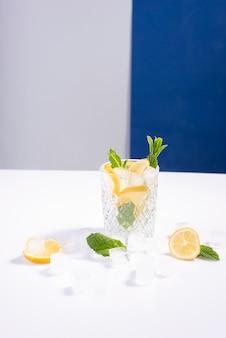흰색 파란색 배경에 레몬, 민트, 얼음 조각이 있는 유리잔에 얼음을 넣은 창의적인 여름 칵테일.