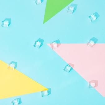 Творческая летняя композиция с кубиками льда и красочными бумажными формами. минимум сверху вниз.