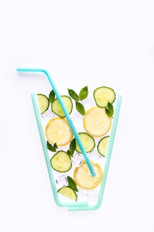 Creative summer drink composition. with lemon slices, mint leaves, cucumber and ice cubes on white