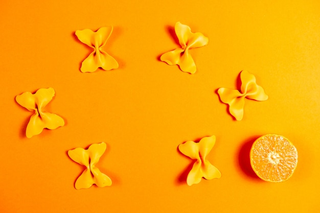 Creative summer layout made of clementines and colored pasta semolina papillon on  orange background