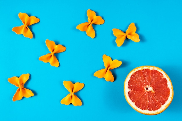 Creative summer layout made of grapefruit and colored pasta semolina papillon on blue background.