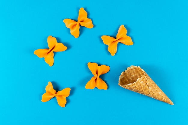 Creative summer layout made of ice cream cone, waffle cones and colored pasta semolina