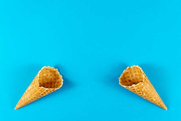 Creative summer layout made of ice cream cones, waffle cones on bright light blue background.