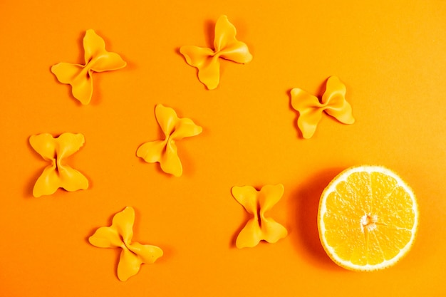 Creative summer layout made of oranges and colored pasta semolina papillon on  orange background