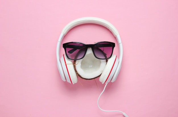 창의적인 여름 미니멀리즘. 코코넛, 선글라스, 핑크 파스텔 배경에 헤드폰. 평면도