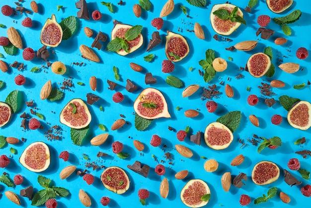 천연 재료로 만든 창의적인 달콤한 음식 구성. 초콜릿, 딸기, 아몬드, 무화과, 민트가 있는 여름 패턴 - 파란색 배경에 에너지 스낵 재료. 평면도.