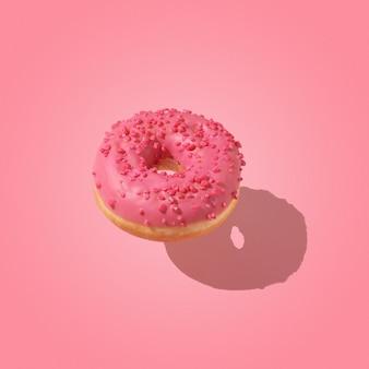 창의적인 달콤한 음식 개념입니다. 분홍색 배경 위에 떠 있는 분홍색 도넛.