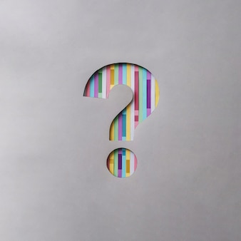 Creative symbol question mark cut out in a gray background with colored stripes concept of the idea of finding an answer and information, help, communication
