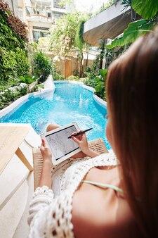 Творческая талантливая молодая женщина расслабляется у бассейна и рисует модный эскиз на планшетном компьютере