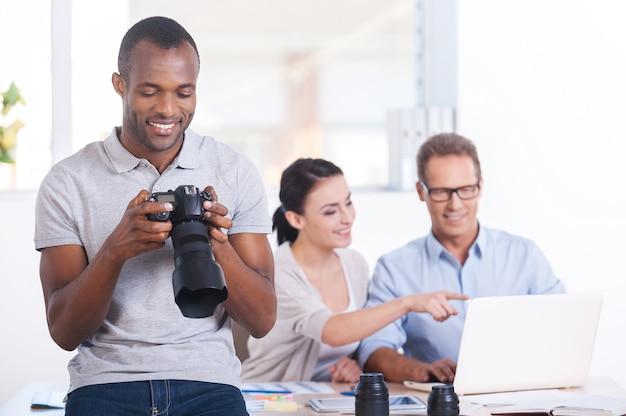 직장에서 크리에이 티브 팀입니다. 두 사람이 배경 작업을 하는 동안 카메라를 들고 웃고 있는 잘생긴 젊은 아프리카 남자