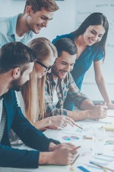 Творческий коллектив за работой. вид сбоку на пятерых веселых деловых людей в элегантной повседневной одежде, которые обсуждают что-то, глядя на графики и диаграммы